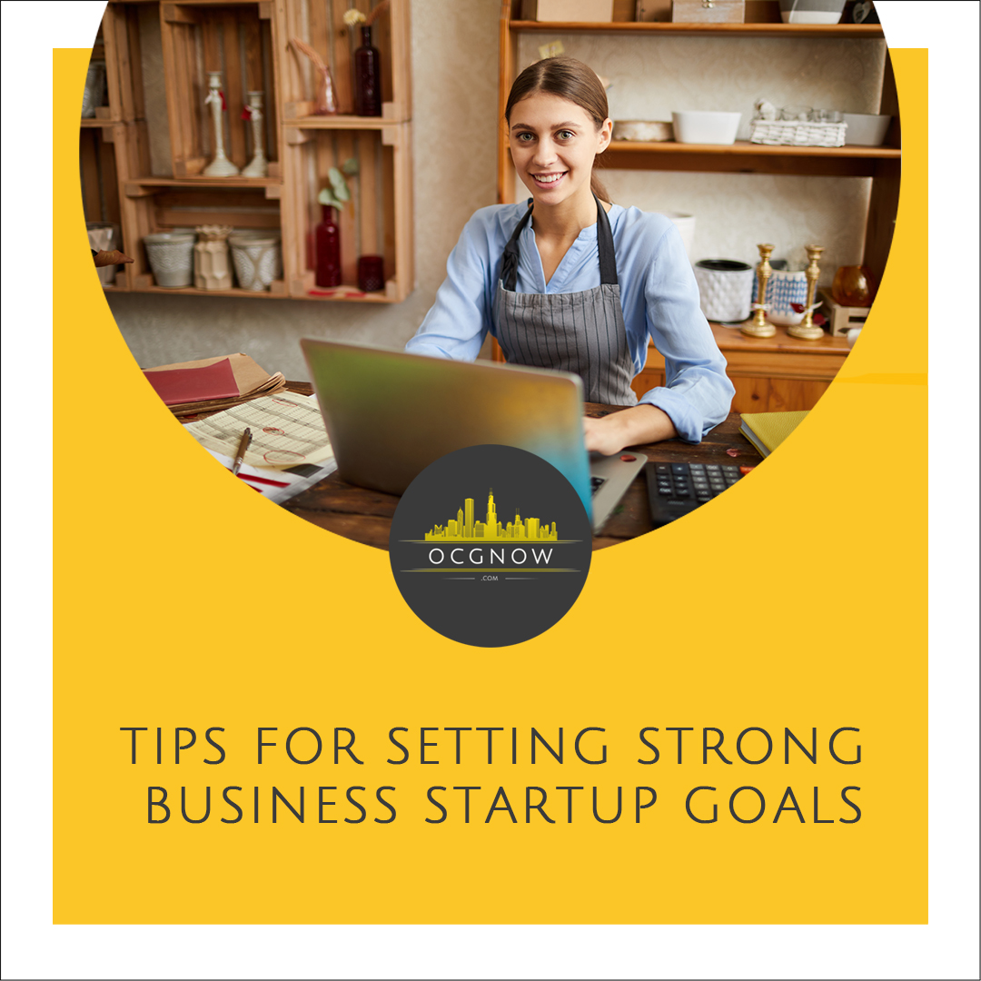 Female small business owner working at desk depicting setting small setting business startup goals